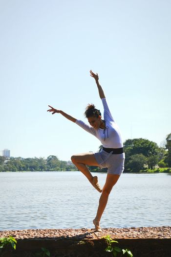 Full length of woman dancing by river against clear sky