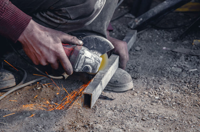 Low section of worker using power tool on metal at workshop