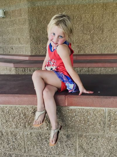 Portrait of cute girl sitting on retaining wall