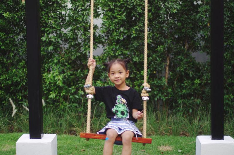 Portrait of happy girl sitting on a swing