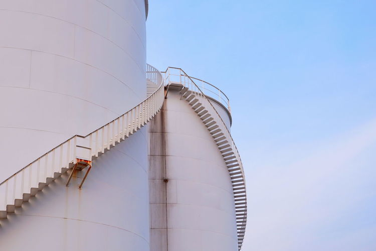 Curve pattern of spiral staircase on surface of fuel tanks against cloud and blue sky background in evening time Metal Old Railway White Chemistry Gas Outdoor Industry Business Industrial Space Low Angle View Curve Lines EyeEm Selects Factory Oil Industry Industry Working Oil Pump Natural Gas Storage Tank Fuel Storage Tank Silo Oil Stairway Oil Refinery Stairs Steps