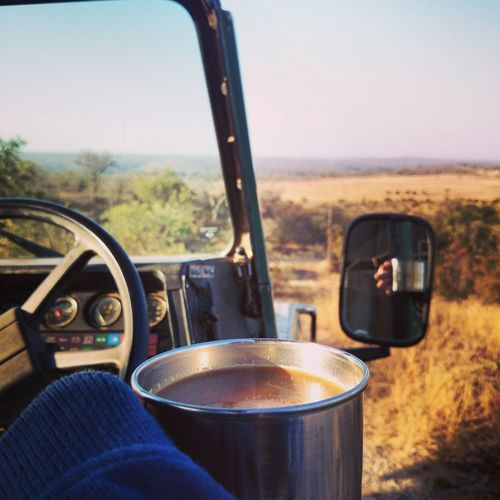 Cropped Hand Holding Coffee In Sports Utility Vehicle