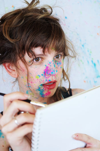 Close-Up Of Woman Covered In Powder Paint Holding Paintbrush And Notebook