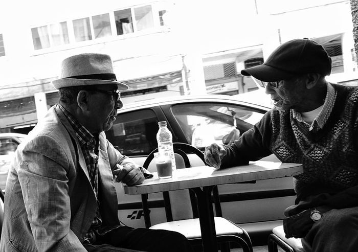 TO EACH HIS HAT. People Street Senior Adult Streetphotography Drink City Street Day Coffee Coffee Time Cofeeshop Cofee Hour Friendship Talking Black And White Photography Candid Photography