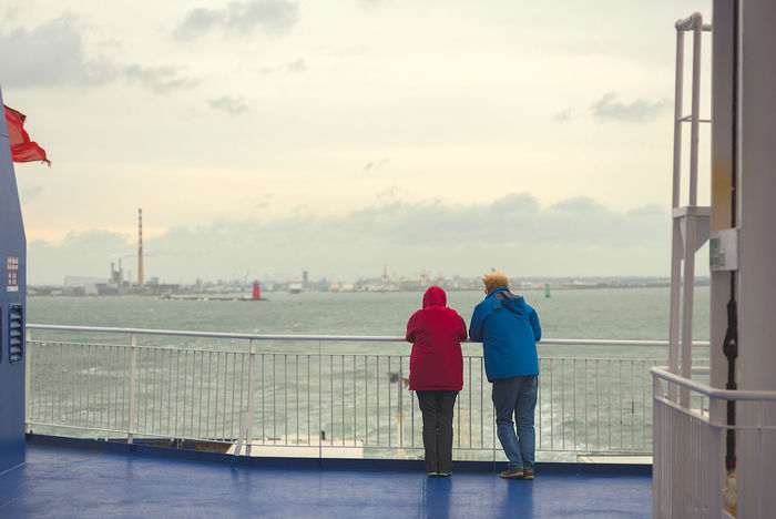 Elderly couple on the outside deck of the Dublin to Holyhead ferry watching Dublin disappear in the distance at sunset. Departing Dublin Ferry Ferry Crossing Beauty In Nature Casual Clothing Cloud - Sky Day Horizon Over Water Leaving Love Men Nature Outdoors People Real People Rear View Sailing Sea Sky Togetherness Two People Watching Water Women
