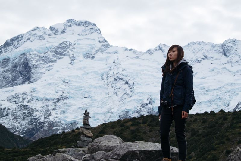 Full length of young woman standing on snowcapped mountain