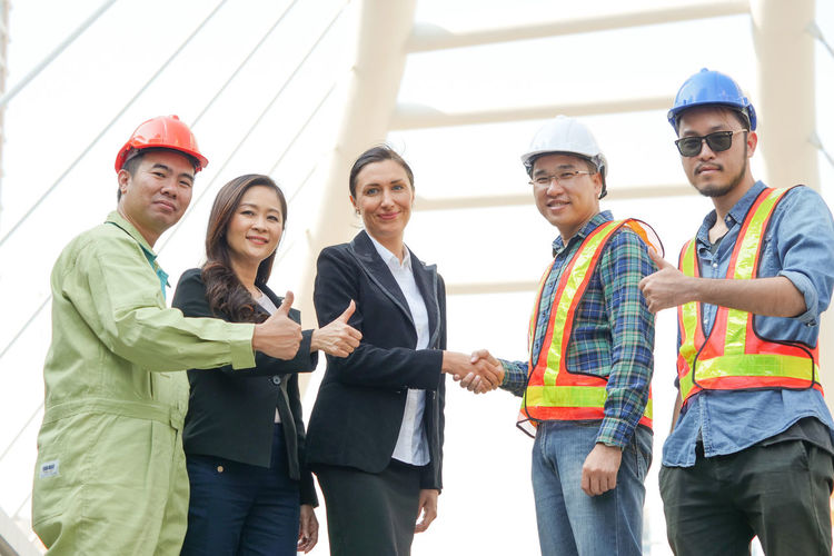 Portrait Of Business People With Engineers Standing Against Bridge