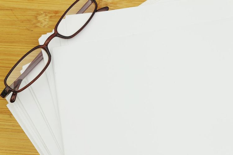 Stack of papers with eye glasses Copyspace Spectacle Eyeglasses  Background Blank NotePad Wooden Eyesight Eyeglasses  Copy Space Close-up Lined Paper