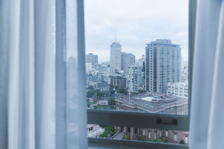 Cityscape against sky seen through glass window