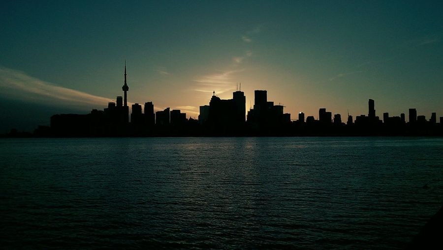 Silhouette buildings by river in city against sky during sunset
