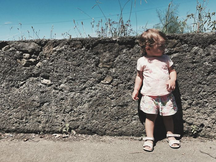 Full Length Of Child Standing Against Concrete Wall During Sunny Day