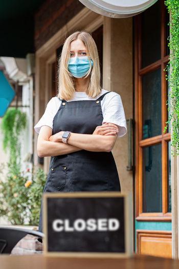Caucasian waitress woman wearing medical mask, cafe closed. coronavirus covid-19 pandemic