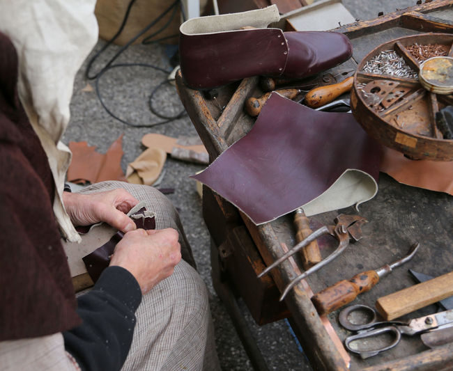 old cobbler while repairing the shoe with a piece of leather Artist Cobblers' Shop... Firenze Leather Shoe Shoemaker Workshop Cobbler Cobbler At Work Cobbler Shop Cobbler's Tools Craft Craftman Florence Italy Occupation People Real People Shoe Making Shoemaking Shoes Tools Wokshop Working Workshops