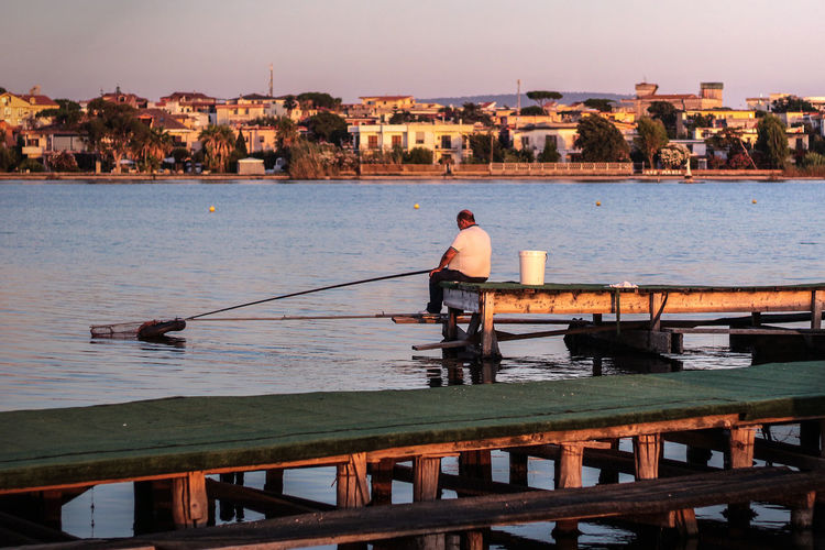 Man fishing while sitting on pier in city during sunny day
