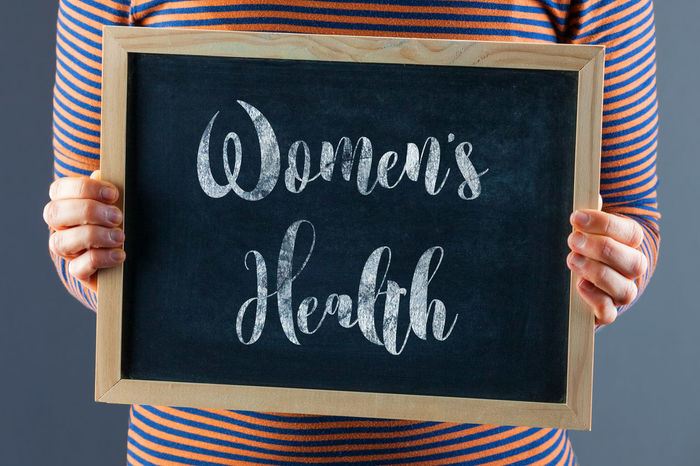 Female hands holding small black chalkboard in front of the body with text saying Women's Health Sign Woman Women's Health Adult Awareness Blackboard  Blackboard  Board Body Part Casual Clothing Chalkboard Close-up Communication Hand Handwriting  Health Holding Human Body Part Human Hand Indoors  Message Midsection One Person Standing Striped Text Western Script