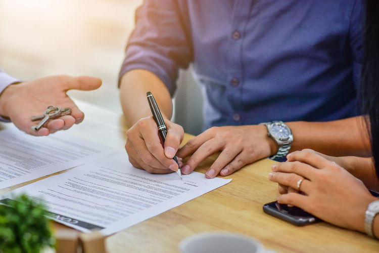 Cropped hand of real estate agent holding key by customer signing contract on table