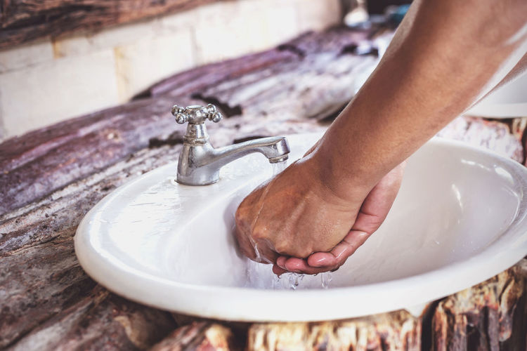 Person washing hands at faucet