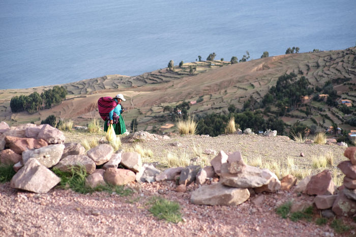 a view from the pachatata hillside at Amantani island overlook the lake titicaca. Amantani Island Beauty In Nature Full Length Lake Titicaca Landscape Mountain Nature Outdoors Quechua Real People Rock - Object Scenics South America