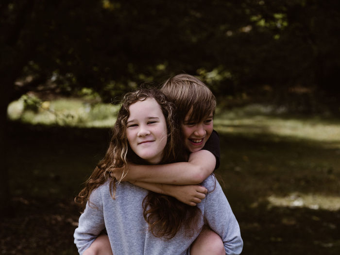Portrait of smiling sister piggybacking brother in forest