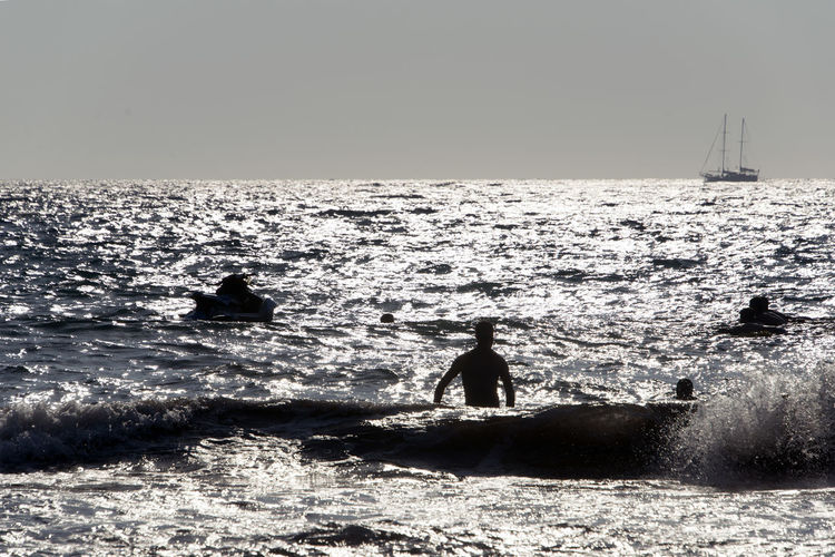 SILHOUETTE OF People playing, swimming in the waves in the island of Patmos, Greece in summer time Beauty In Nature Day Horizon Horizon Over Water Land Leisure Activity Lifestyles Men Motion Nature Outdoors People Real People Scenics - Nature Sea Silhouette Sky Water Wave