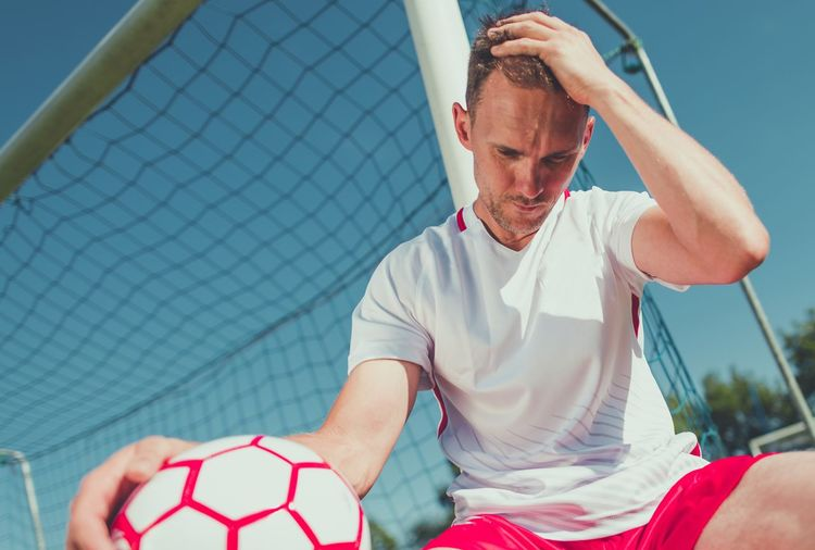 Low angle view of worried soccer player sitting by goal post against sky