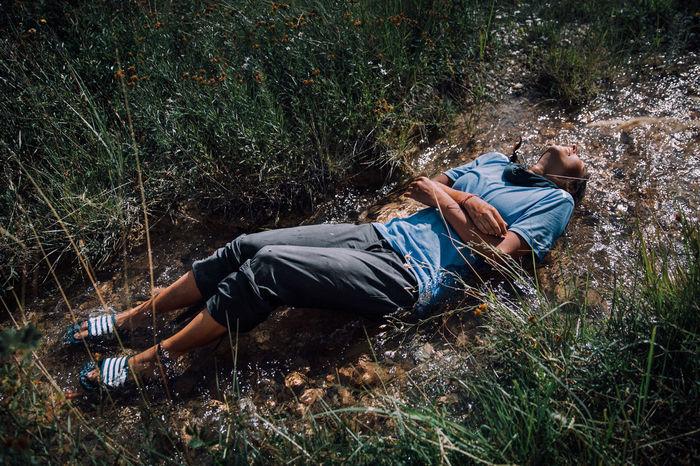 HIGH ANGLE VIEW OF MAN LYING DOWN ON LAND
