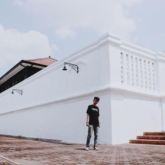 Full length of man standing on building against sky