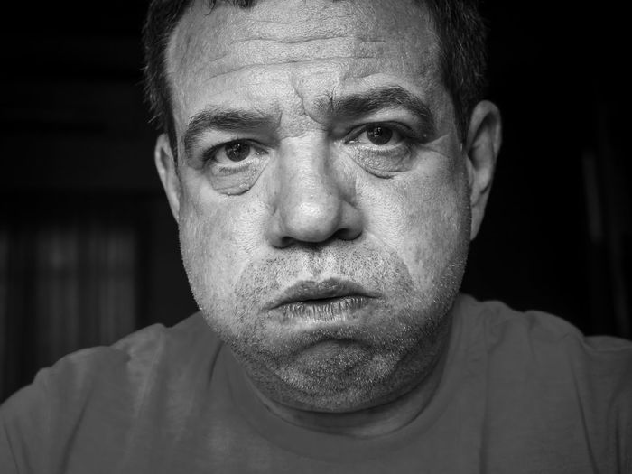 Close-up portrait mature man making face in darkroom