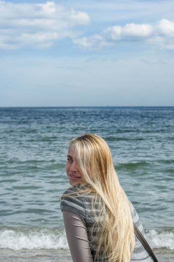Side view portrait of young woman at beach against sky