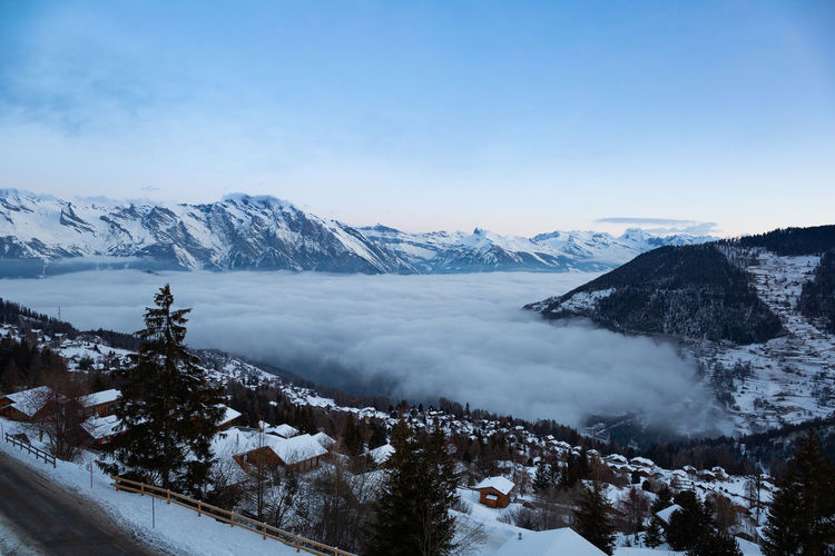 The swiss alps village of la tzoumaz, valais, switzerland, with fog covering the valley down below.