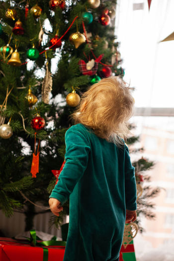 Cute little kid looks at christmas tree decorated with toys and garland. new year and christmas.