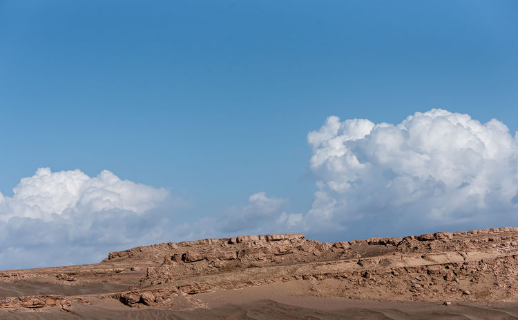 Panoramic view of desert against blue sky