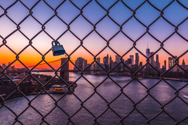 Lock hanging on chainlink fence over river in city during sunset
