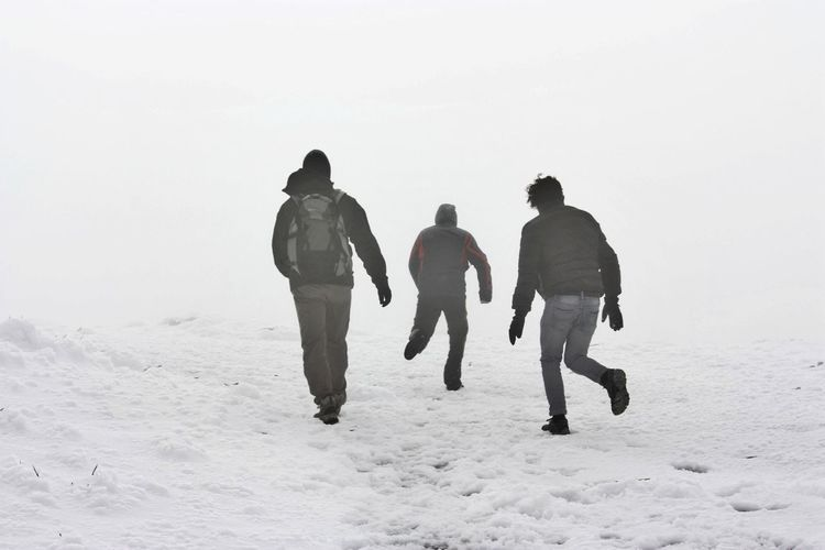Rear view of silhouette people walking on snow covered landscape