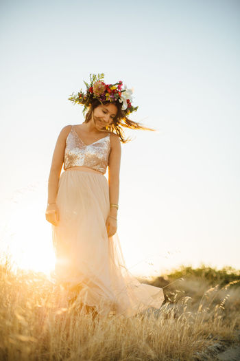 Woman Wearing Flowers Standing On Field Against Sky