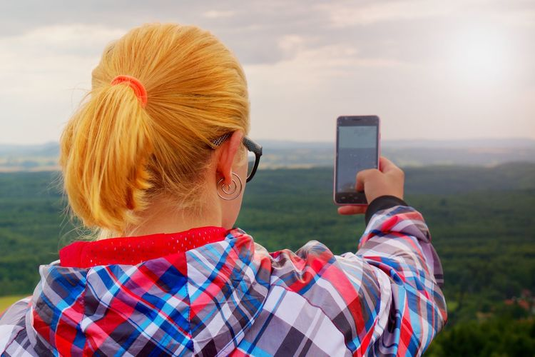 Hiking blonde woman taking photo with smart phone at mountains.