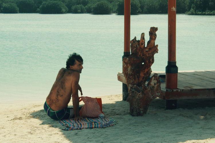 Man sitting on beach by sea