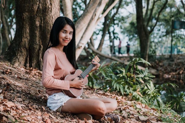 Happy woman smiling and playing ukulele under tree at park in summer. Young Woman White Vintage Ukulele Summer Style Smiling Pretty Portrait Plays Playing Play Performance People Outdoor Nature Musician Music Modern Little Listening Listen Lifestyle Length Instrument Hipster Happy Happiness Half Guitar Girl Female Daughter Cute Concept City Child Caucasian Bossanova Beautiful Background Attractive Asian  Acoustic