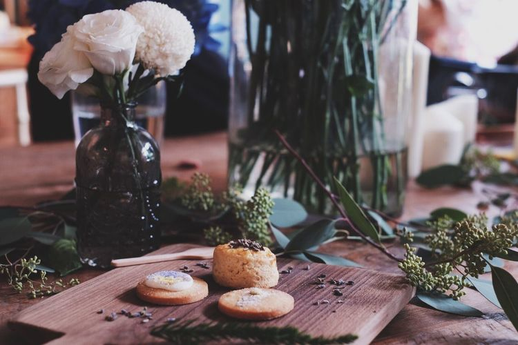 Close-up of cookies on cutting board by flowers vase on table