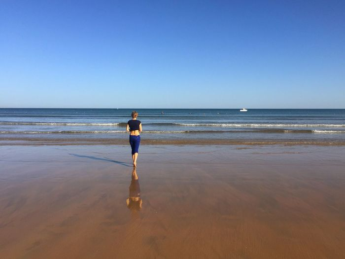 Rear view of woman running on beach against clear sky