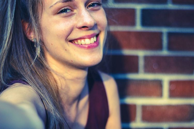 Close-up portrait of smiling woman against brick wall