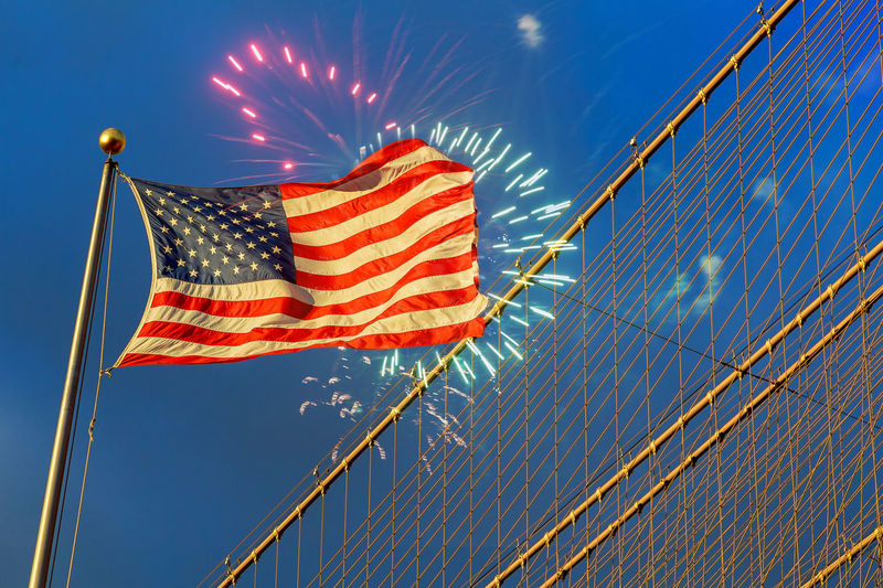 Low angle view of american flag against firework display