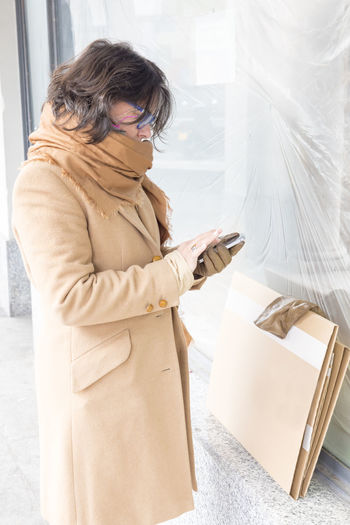 Side View Of Woman Using Phone While Standing In Store