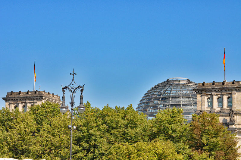 Low angle view of trees by the reichstag against clear blue sky