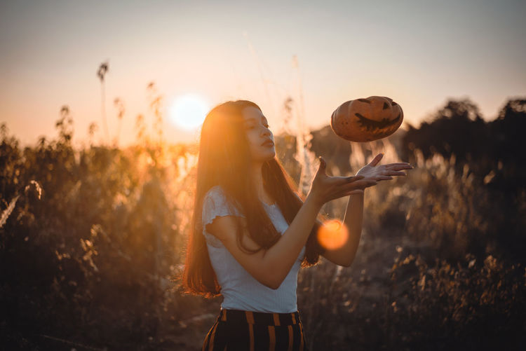 Midsection of woman standing on field against sky during sunset