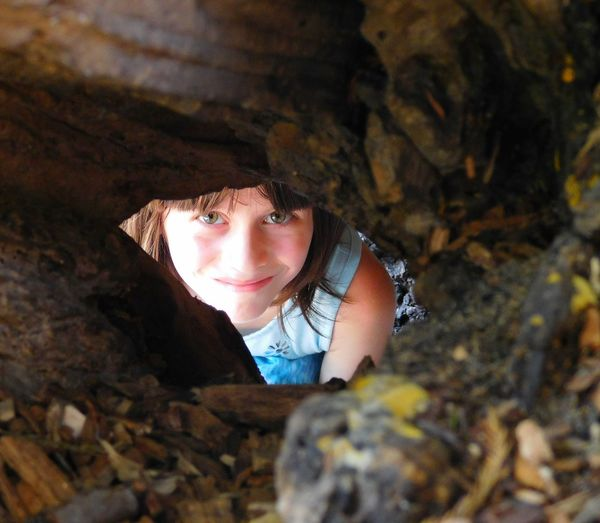 High angle portrait of girl seen through tree hole
