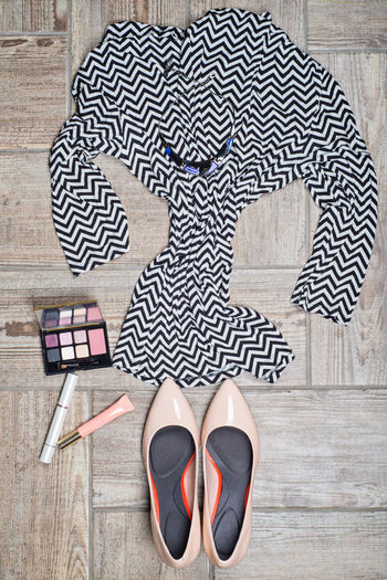 Flat lay of womenswear and make-up on wooden floor
