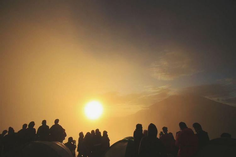 Silhouette people enjoying on mountain against orange sun in sky