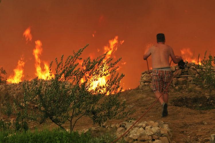 Rear view of shirtless man standing against orange sky