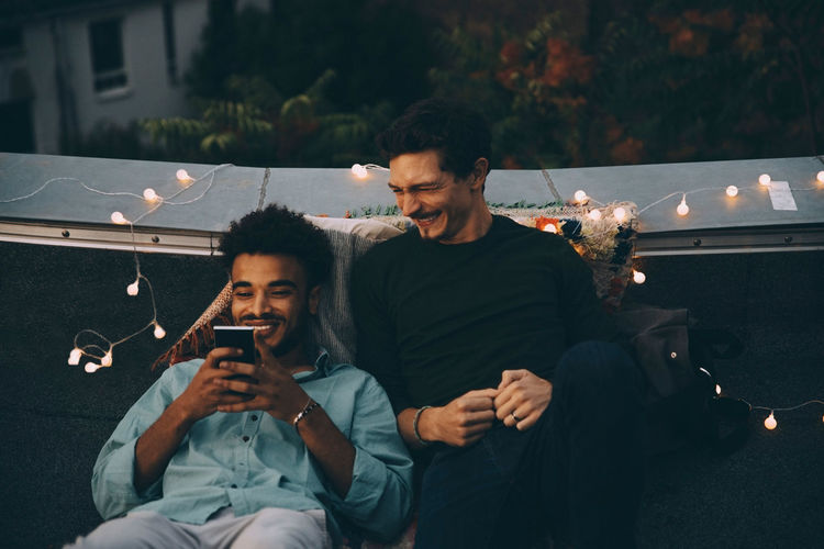 Young couple sitting on smart phone at night